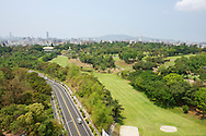 The green fairways of the Kaohsiung Country Club contrast with the city skyline