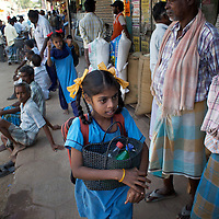 """Vijyashree (foreground) and Vijita on their way to school after catching a shared rickshaw from their home village of Thazanguda into Cuddalore...Vijita (age 14) and Vijyashree (age 11) Viswanathan lost their mother and brother to the tsunami in 2004. They continue to live in the fishing village of Thazanguda with their father Viswanathan, his second wife Kayalvizhi and their two children Sanjay (age 3) and Monica (age 1). ..Until the beginning of the 2009 academic year in June, Vijita and Vijyashree attended the local Thazanguda school. This village school teaches pupils only until the 8th Standard and with Vijita now entering the 9th, it was decided that the two daughters remain together and both travel 3km to the local town school: the Government Girls High School, Venugopalapuram in Cuddalore. ..At the same time Viswanathan decided he would cease day-to-day care of his daughters and place them in the Government Home for Tsunami Children, also in Cuddalore. This was not a move welcomed by either Vijita or Vijyashree and one afternoon after just two weeks at the orphanage, the two girls ran away. At roll call in the orphanage that evening the alarm was sounded and the two sisters were eventually located in Thazanguda waiting for their father and Kayalvizhi who were both away at the time. Realising his daughters' unhappiness, Viswanathan then took them out of the Government home. ..According to her class teacher, Vijita often compares her step-mother to her mother and concludes that she wants her mother back. Vijita confides in her teachers that her stepmother is forever demanding that she and her sister Vijyashree undertake housework. This frustration at home is tempered by the genuine love both sisters have for their father and two younger siblings Sanjay and Monica. Vijita expresses a lonelyness without her mother. Pushpavalli concludes that """"Vijita wants something else beyond the love of her father and sister"""". ..Viswanathan appears genuinely to want the best f"""