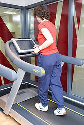 Woman using the treadmill at her sports leisure centre,