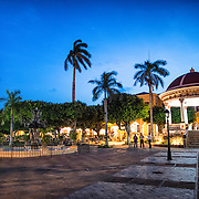 A fountain and pergola stand in the middle of Parque Central at dusk. Parque Central is the main square and the historic heart of Granada, Nicaragua.