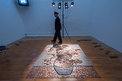 "© Licensed to London News Pictures. 01/04/2019. LONDON, UK.  ""Bureau de Change"", 1987, by Rose Finn-Kelcey is unveiled at Tate Britain.  Coinciding with ""The EY Exhibition:  Van Gogh and Britain"", the live installation consists of £1,000 worth of coins laid out on the floor in the image of Vincent Van Gogh's ""Sunflowers"".  The installation is overseen each day by an actor posing as a security guard, with visitors viewing the scene from a platform and will be in place 1 Aptil to 11 August 2019.  Photo credit: Stephen Chung/LNP"