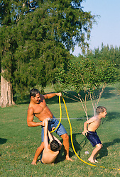 Good looking man squirting water from a garden hose at young boy while another boy helps direct the water