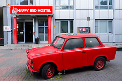 Exterior of budget hostel with red East German Trabant car outside in Berlin Germany