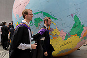 Beneath the sculpture by Turner Prize-winning artist Mark Wallinger entitled The World Turned Upside Down, new graduates straight after their graduation ceremonies meet family and friends outside the London School of Economics LSE, on 22nd July 2019, in London, England. The World Turned Upside Down is a large political globe, four metres in diameter, with nation states and borders outlined but with the simple and revolutionary twist of being inverted. Most of the landmasses now lie in the 'bottom' hemisphere with the countries and cities re-labelled for this new orientation.