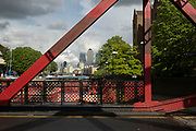 View looking through an old bridge in Wapping towards Canary Wharf financial district. on 24th May 2021 in London, United Kingdom. The bridge is a very old tilt bridge designed by Marc Brunel.