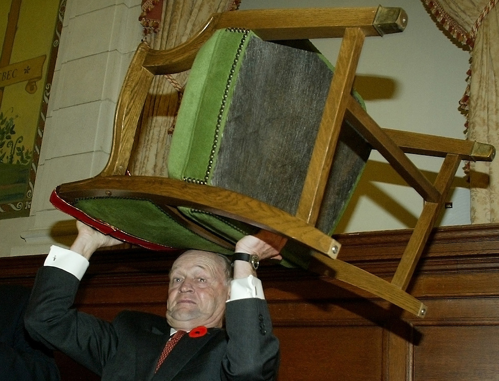 Canadian Prime Minister Jean Chretien lifts his House of Commons chair over his head during his last caucus meeting as Liberal party leader in Ottawa, November 5, 2003.  Chretien will retire after 40 years of politics, 10 of those as prime minister.   REUTERS/Jim Young