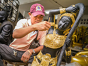"12 NOVEMBER 2012 - BANGKOK, THAILAND:   A man finishes a statue of Shiva at a workshop Bamrung Muang Street in Bangkok. Although Hindu, Shiva also figures prominently in Thai Buddhism. Thanon Bamrung Muang (Thanon is Thai for Road or Street) is Bangkok's ""Street of Many Buddhas."" Like many ancient cities, Bangkok was once a city of artisan's neighborhoods and Bamrung Muang Road, near Bangkok's present day city hall, was once the street where all the country's Buddha statues were made. Now they made in factories on the edge of Bangkok, but Bamrung Muang Road is still where the statues are sold. Once an elephant trail, it was one of the first streets paved in Bangkok. It is the largest center of Buddhist supplies in Thailand. Not just statues but also monk's robes, candles, alms bowls, and pre-configured alms baskets are for sale along both sides of the street.    PHOTO BY JACK KURTZ"