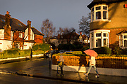 A pedestrian carrying an umbrella with a child on a scooter, walks along a south London residential street, passing sunlit Edwardian period homes after heavy rainfall, on 25th February 2020, in London, England.