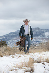 rugged cowboy carrying a saddle through a snowy mountain range