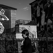 """A woman walks past murals depicting scenes from the Troubles found in the Bogside, a Catholic enclave of Londonderry, Northern Ireland. This city is considered a """"front-line"""" of Britain's push to leave the E.U. Northern Ireland, September 2019"""