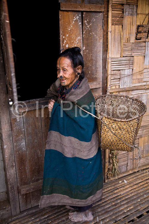 Atta Yadd, an elderly Apatani tribal grandmother in her village of Hijja in the northeastern state of Arunachal Pardesh, India. The Apatani minority, one of hundreds spread across northern India are known to have come originally from nomadic Mongolian ancestry, they settled in north eastern India and now are best known for being foresters, farmers specialising in the cultivation of Bamboo.
