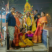 A family bringing a holy deity from their temple to get it blessed at a holy river.