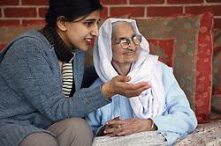 Granddaughter sitting with her Sikh elderly Grandmother,