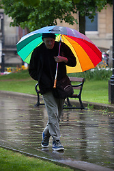 © Licensed to London News Pictures. 14/05/2015. Bristol, UK. A man with a rainbow coloured umbrella braving the wet weather next to College Green in Bristol today, Thursday 14th May 2015. Photo credit : Rob Arnold/LNP