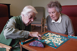 Two elderly women playing game of scrabble at day centre,