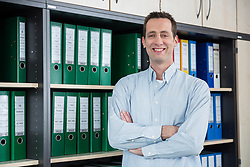 Businessman standing filing cabinet office relaxed