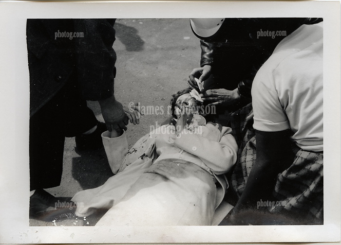 """Injured Woman on sidewalk being treated. On-The-Scene Accident Photograph, Elm & Orchard Streets New Haven CT circa December 1956. This photo is part of a set of 15 images captured of this accident by photographer Robert F. Anderson, Legal Photo Service. A scan of a 3.5""""x5"""" original lab print, negative or precise records not found. Not yet restored from deterioration, date is approximate."""