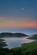 Moon at dawn over green hills in Spring and Whale Rock Reservoir, near Cayucos, Central Coast, California