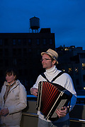 New York, NY - 30 April 2012. An accordionist warms up on the High Line near 30th Street prior to the start of the Parade of Illumination, opening the 2012 PEN World Voices Festival.