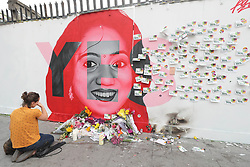 A woman kneels infront of a mural of Savita Halappanavar in Dublin as votes are counted in the referendum on the 8th Amendment of the Irish Constitution which prohibits abortions unless a mother's life is in danger.