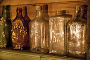 Old glass bottles are displayed on a shelf in an old coastal cottage