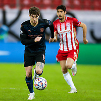 PIRAEUS, GREECE - NOVEMBER 25: John Stones of Manchester City and Andreas Bouchalakis of Olympiacos FC during the UEFA Champions League Group C stage match between Olympiacos FC and Manchester City at Karaiskakis Stadium on November 25, 2020 in Piraeus, Greece. (Photo by MB Media)