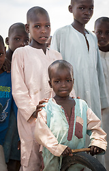 31 May 2019, Mokolo, Cameroon: A young boy holds a toy consisting of a small stick and a bike wheel. One of 20 sites for Internally Displaced People in the Far North region of Cameroon, Zamay currently hosts 4,102 IDPs from the border area between Nigeria and Cameroon. Fleeing the atrocities of Boko Haram, and cross-border fighting between Boko Haram and Cameroonian coalition forces, the IDPs have settled alongside the host community of 32,000 people in Zamay.