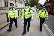 Police escort Extinction Rebellion 'crime scene investigators' in white suits and masks walk along Whitehall into Parliament Square to investigate areas of ecocide in a performance on 7th September 2020 in London, United Kingdom. The 20 investigators were protesting at the Brazilian government's alleged involvement in ecocide in the Amazon, and the UK government's ecocide along the HS2 route. Extinction Rebellion is a climate change group started in 2018 and has gained a huge following of people committed to peaceful protests. These protests are highlighting that the government is not doing enough to avoid catastrophic climate change and to demand the government take radical action to save the planet.