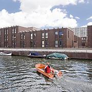Nederland Amsterdam 15-09-2010 20100915..Nieuwbouw wijk IJburg, woningen in het hogere segment. Jongeman vaart in motorbootje door de wijk, langs de nieuwbouwwoningen en de boten die aan de kade liggen. IJburg is een woonwijk in aanbouw in het oosten van de gemeente Amsterdam, in de Nederlandse provincie Noord-Holland. Kenmerkend aan de in het IJmeer gelegen wijk is dat deze op kunstmatige eilanden is gebouwd. IJburg maakt onderdeel uit van het stadsdeel Oost. Holland, The Netherlands, dutch, Pays Bas, Europe , Yburg, het Ij, Het Y, , waterstand, watersysteem, waterveiligheid, waterveiligheid en gebiedsontwikkeling, waterwijk, waterwijken, waterwoning, waterwoningen, wijk, wijken, wonen aan het water, woning, woningaanbod, woningbouw, woningen, woningmarkt, woningvoorraad, woonbuurt, woonbuurten, woonlast, woonlasten, woonwijk, woonwijken..Foto: David Rozing