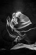 Swirling sandstone walls of Upper Antelope Canyon near Page, AZ. Black and white photographic art.
