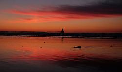 A colourful sky above Blyth lighthouse off the Northumberland coast before sunrise.