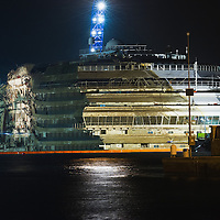 ISOLA DEL GIGLIO, ITALY - SEPTEMBER 17:  The Costa Concordia severely damaged is seen at 4am  Rome Time after the succesful completion of the parbuckling operation on September 17, 2013 in Isola del Giglio, Italy. Work begins today to right the stricken Costa Concordia vessel, which sank on January 12, 2012. If the operation is successful, it will then be towed away and scrapped. The procedure, known as parbuckling, has never been carried out on a vessel as large as Costa Concordia before.  (Photo by Marco Secchi/Getty Images)