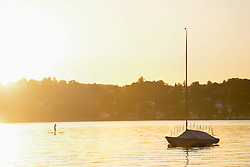 Silhouette of a woman paddleboarding in lake, Bavaria, Germany