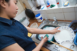 Teenage girl doing the washing up at home after a meal,