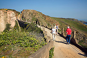 Tourists walk across La Coupee road, Island of Sark, Channel Islands, Great Britain