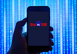 Person holding smart phone with Baidu logo displayed on the screen. EDITORIAL USE ONLY
