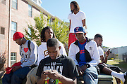Grambling State University students sit outside between classes while the fire alarm goes off in the dorm across the street in Grambling, Louisiana on October 23, 2013.  (Cooper Neill for The New York Times)