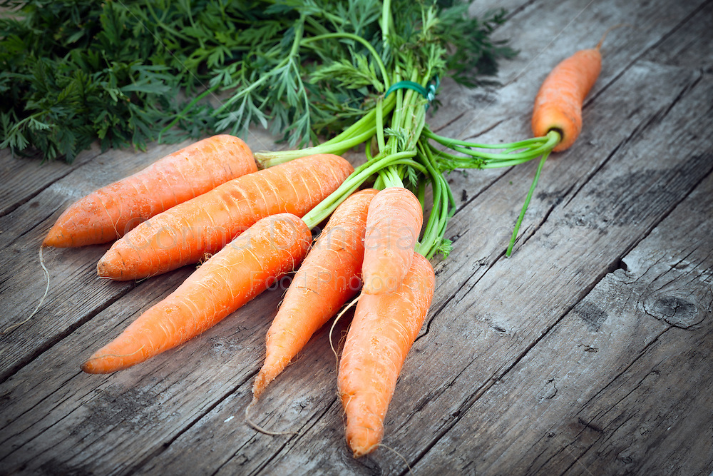 Freshly harvested carrots, biological agriculture product, on old wooden table.