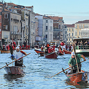"""VENICE, ITALY - JANUARY 06:  Rowers dressed in costume race along the Grand Canal for the """"Befana"""" Regatta on January 6, 2014 in Venice, Italy. In Italian folklore, Befana is an old woman who delivers gifts to children throughout Italy on the feast of the Epiphany on January 6 in a similar way to Saint Nicholas or Santa Claus.  (Photo by Marco Secchi/Getty Images)"""
