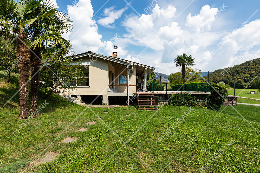 Villa with patio and palm in the countryside surrounded by green lawn. Nobody inside