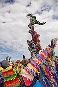 Costumed revelers climb a greased pole to grab a chicken on the top during the Faquetigue Courir de Mardi Gras chicken run on Fat Tuesday February 17, 2015 in Eunice, Louisiana. The traditional Cajun Mardi Gras involves costumed revelers competing to catch a live chicken as they move from house to house throughout the rural community.