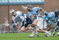 28 March 2009: North Carolina Tar Heels midfielder Cryder DiPietro (22) is upended by long stick midfielder Charlie Wiggins (9) during a 10-9 overtime win over the Johns Hopkins Blue Jays on Fetzer Field in Chapel Hill, NC.