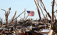 An American flag flies over the remains of the neighborhood near the Plaza Towers elementary school in Moore, Oklahoma May 22, 2013. A massive tornado tore through a suburb of Oklahoma City, wiping out whole blocks and killing at least 24.   REUTERS/Rick Wilking (UNITED STATES)