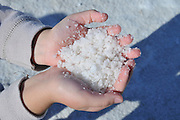 Hands of a young girl holding sea salt from the dehydration pools