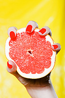 caucasian woman hand holding a grapefruit studio on yellow background