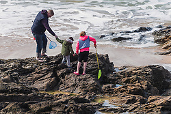A father and his two children explore the rock polls at Fistral Beach in Newquay, Cornwall.