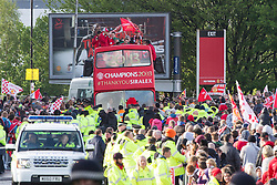 © Licensed to London News Pictures . 13/05/2013 . Manchester , UK . Manchester United trophy parade on Sir Matt Busby Way , from Old Trafford to Manchester City Centre this evening (Monday 13th May) . The team are celebrating their 20th league title win and commemorating the retirement of manager , Sir Alex Ferguson , by carrying the trophy on an opened top bus through the city . Photo credit : Joel Goodman/LNP