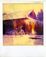 An old bicycle is parked in front of a house. Northern Vietnam, Asia. The polaroid is really outdated and present yellow tones.