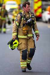 A Firefighter makes his way from the fire to his pump at  at The Mall in Walthamstow in North East London, where a large fire broke out during rush hour this morning and appears to have destroyed the foodcourt and according to a manager escorted by LFB officials at the adjacent Asda, a large amount of stock. London, July 22 2019.