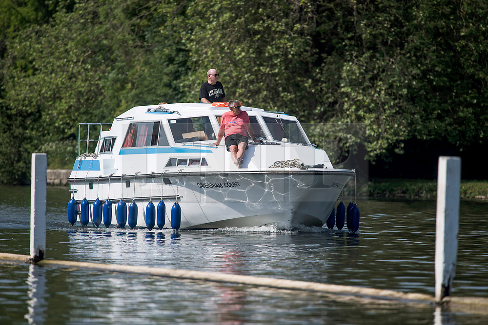 © Licensed to London News Pictures. 15/06/2021. Henley-on-Thames, UK. A man relaxes on the front of a boat as it makes its way along the River Thames at Henley-on-Thames in Oxfordshire on a hot summer's morning. Photo credit: Ben Cawthra/LNP